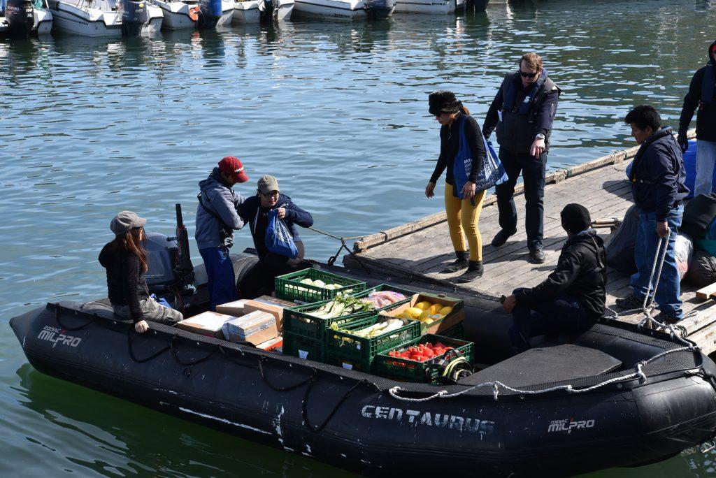En même temps que des passagers, des caisses de fruits et de légumes retournent sur le bateau au port d'Ilulissat. Photo : Véronique Leduc.