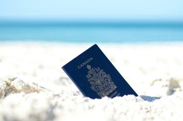 Passeport canadien dans le sable. Photo: Shutterstock