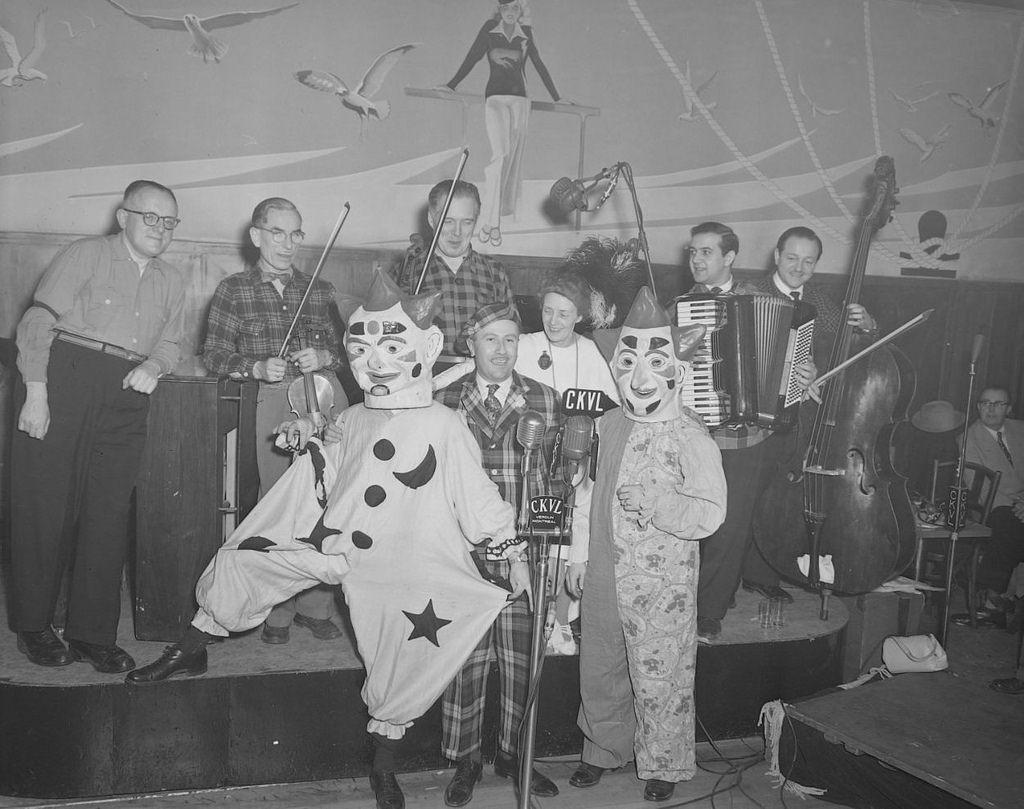 De gauche à droite, Léon Lachance, Oswald, Juliette Béliveau, Claude Séguin et l'orchestre de Adrien Avon sont travestis à la mode des années 1900.Photo: Conrad Poirier.BAnQ